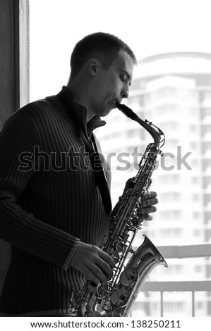 handsome young man playing on saxophone outdoor