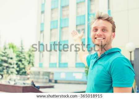 Handsome young man pointing in direction of apartment. New apartment in tall building - stock photo