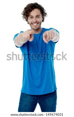 Handsome young man pointing towards camera - stock photo