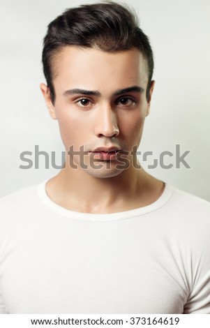 Handsome young man portrait. brunette guy in white t-shirt on a light background Used, clean skin, studio shot, beauty - stock photo