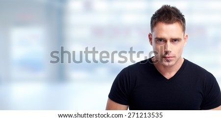 Handsome young man portrait over blue abstract background. - stock photo