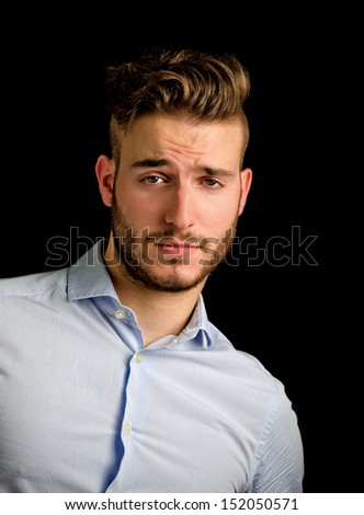Handsome young man portrait with doubtful, unsure expression, isolated on black background - stock photo