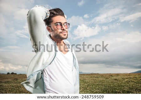 handsome young man posing outdoor, looking away from the camera while fixing his hair. - stock photo