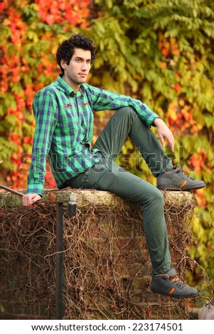 handsome young man posing outdoors against autumn foliage - stock photo