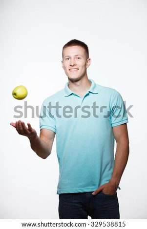 Handsome young man posing with a green apple in his hand isolated on white background