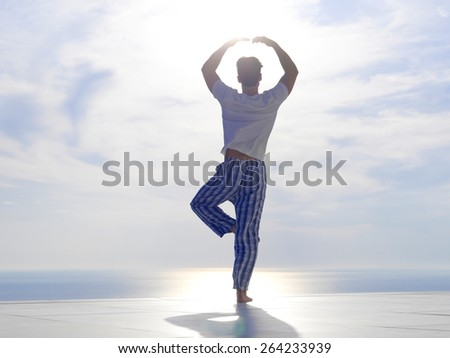handsome young man practicing yoga on in modern home terace with ocean and sunset in background - stock photo