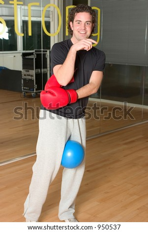 Handsome young man putting on boxing gloves in the gym