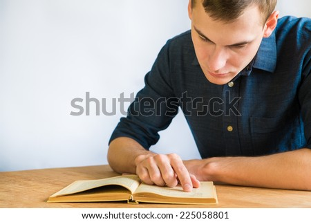 handsome young man reading a book at his desk, on blue background - stock photo