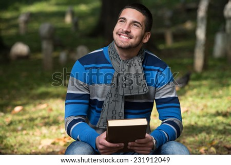 Handsome Young Man Reading A Book In The Park - stock photo
