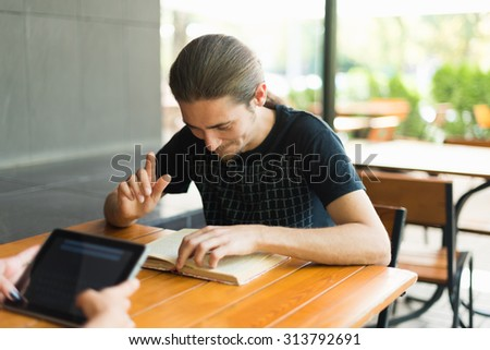Handsome young man reading book outdoors