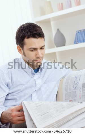 Handsome young man reading newspaper.