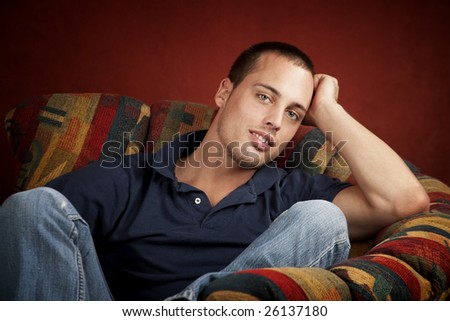 Handsome young man reclining in a colorful chair - stock photo