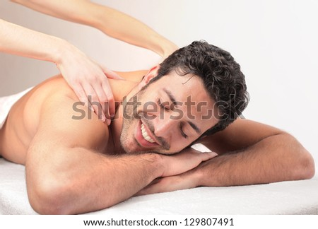 handsome young man relaxes with massage - stock photo