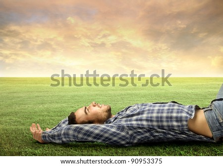 Handsome young man relaxing on a green meadow
