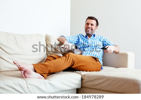 Handsome young man relaxing on a sofa with a bowl of popcorn - stock photo