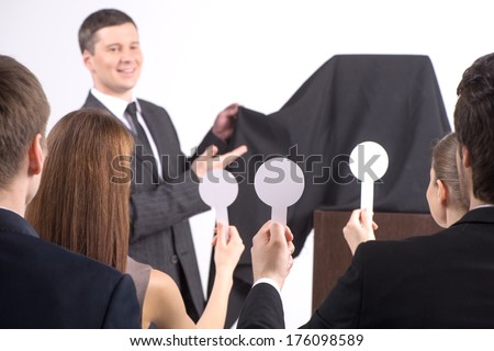 handsome young man removing cover. people at auction lifting paddles together  - stock photo