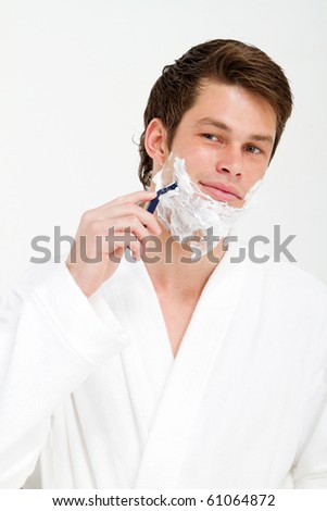 handsome young man shaving in morning - stock photo