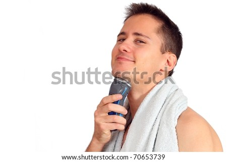 Handsome young man shaving with electric shaver - stock photo