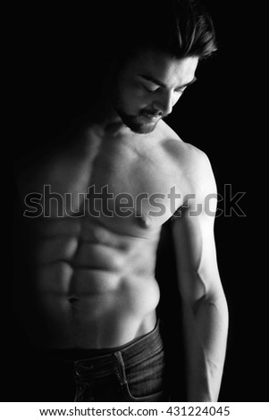 Handsome young man, shirtless, with great body posing over a black background - stock photo