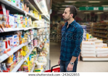 Handsome Young Man Shopping For Fruits And Vegetables In Produce Department Of A Grocery Store - Supermarket - Shallow Deep Of Field - stock photo