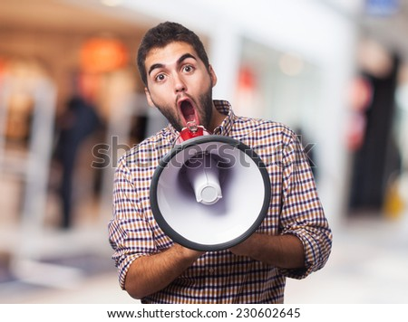 handsome young man shouting through a megaphone - stock photo