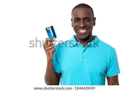 Handsome young man showing his debit card to camera - stock photo