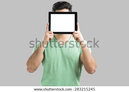 Handsome young man showing something on a tablet, isolated over gray background - stock photo