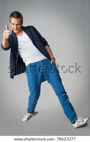 Handsome young man showing thumb up - stock photo
