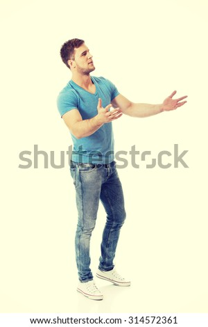 Handsome young man shrugging his hands. - stock photo