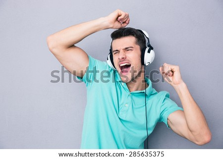 Handsome young man singing in headphones over gray background - stock photo