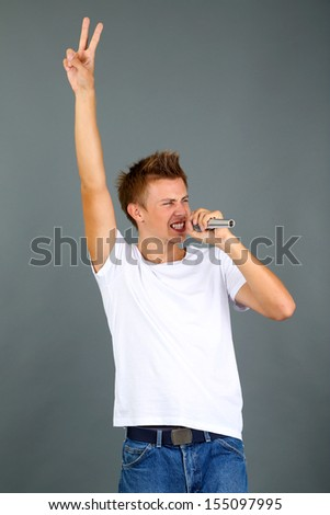 Handsome young man sings on grey background
