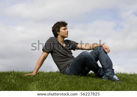 Handsome young man sits on the grass - stock photo