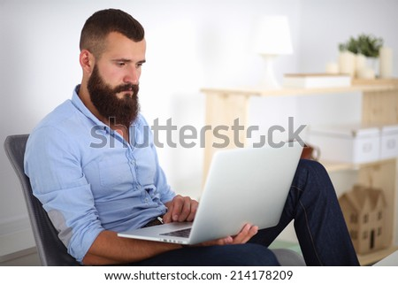 Handsome young man sitting and working on laptop computer.