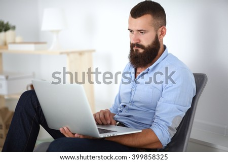 Handsome young man sitting and working on laptop computer - stock photo