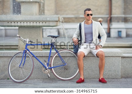 Handsome young man sitting near the fountain with his bicycle beside him - stock photo