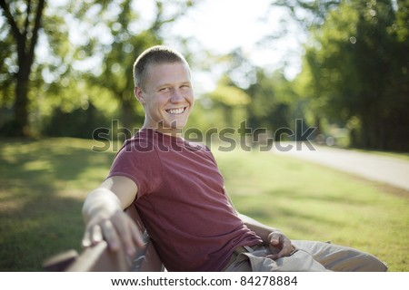 Handsome young man sitting on a bench smiling. Candid. - stock photo