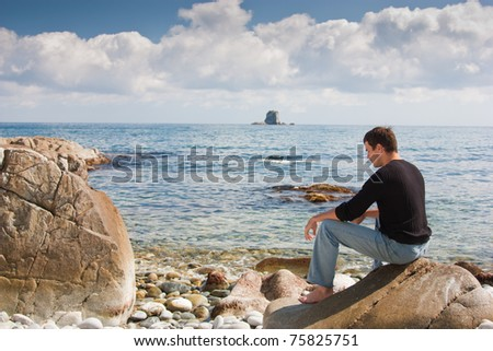 handsome young man sitting on a rock on the beach