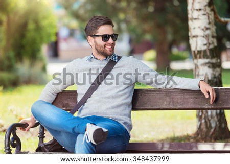 Handsome young man sitting on park bench - stock photo