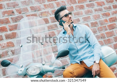 Handsome young man sitting on scooter and talking on the mobile phone - stock photo