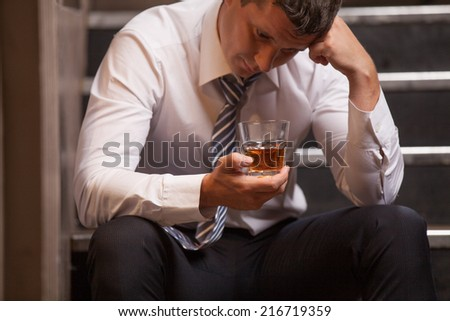 Handsome young man sitting on stairs. closeup of guy drinking whisky and thinking - stock photo