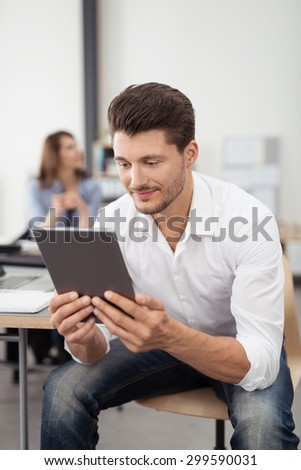 Handsome Young Man Sitting on the Chair with his Body Leaning Forward, Looking at his Tablet Screen Closely on his Hands. - stock photo