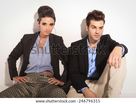 Handsome young man sitting on the floor next to his girlfriend, looking away while she is holding her hands on her hips.