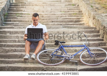 Handsome young man sitting on the stairs and using laptop while his bicycle is beside him - stock photo