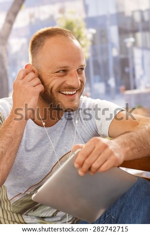 Handsome young man sitting outdoors, using earbuds and tablet computer, looking away. - stock photo