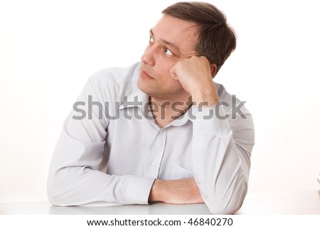 handsome young man sitting pensively on a white - stock photo