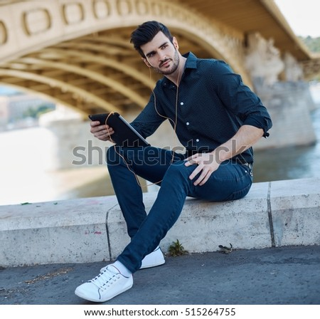 Handsome young man sitting under bridge, using tablet computer, looking away.