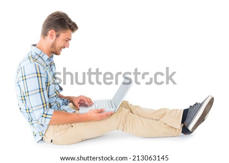 Handsome young man sitting using laptop on white background - stock photo
