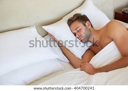 Handsome young man sleeping deeply on a comfortable pillow in a double bed with clean linen and soft pillows
