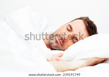 Handsome young man sleeping in white bedding - stock photo
