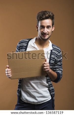 Handsome young man smiling and holding a card board - stock photo